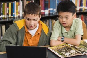 two kids using a laptop to learn